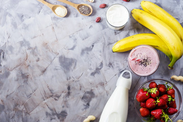 Ingredients for cooking smoothies from strawberries, bananas, milk, yogurt, chia seeds, sesame and peanuts. Healthy eating breakfast. Background, copyspace. Top view, flat lay