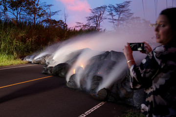 A news reporter takes pictures of the Kilauea lava flow that crossed Pohoiki Road near Highway 132, near Pahoa, Hawaii