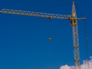Single construction crane isolated on blue sky