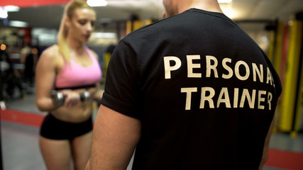 Personal trainer instructing attractive girl how to do dumbbell lifts properly