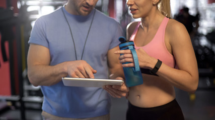 Sport woman discussing workout program with personal trainer, using tablet