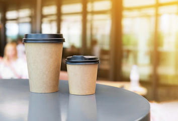Two Paper cup of takeaway coffee on the table. Place for your text or logo.