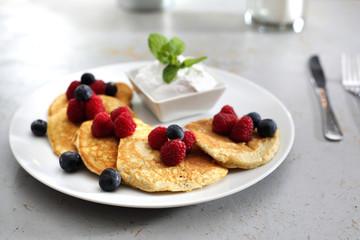 Śniadanie.   Porcja smakowitych placuszków udekorowanych owocami malin i borówek, podanych z sosem jogurtowym
