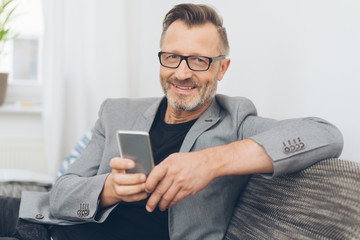 Smiling mature man sitting on sofa with phone