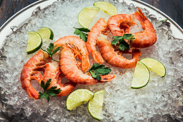 Shrimp with ice with lime and salad on the plate. On wooden background
