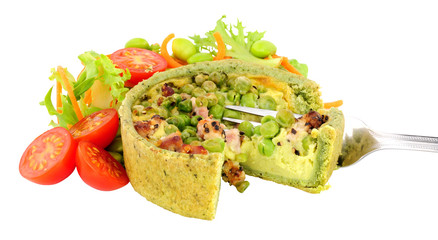 Pea and pancetta filled savoury quiche with fresh simple salad isolated on a white background