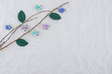 Brown branch decorate with blue tone rose paper flowers and green leaves on muslin fabric with copy space
