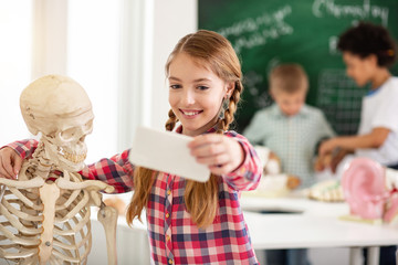 Happy smile. Cheerful positive girl smiling into the camera while taking a selfie with the skeleton