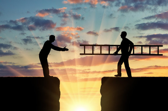 A silhouette of a man carries a ladder to another man who is on the other side of the abyss