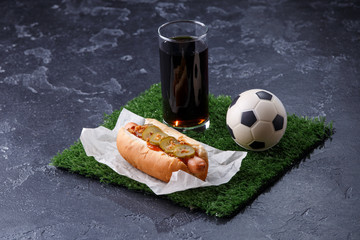 Photo of glass of beer, green grass with soccer ball, hotdog