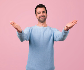 Handsome man presenting and inviting to come on pink background