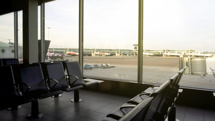 Empty seats of departure lounge airport, view of runway through window, travel