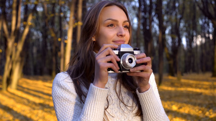 Lady admiring autumn, trying to capture moment with old vintage camera, hobby