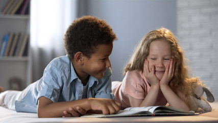 Little girl and her afro-american friend having fun while learning to read book