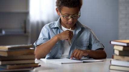 Thinking boy sitting with blank notebook table, writing homework essay, school