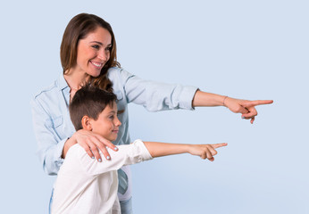 Mother and daughter pointing finger to the side and presenting a product on blue background