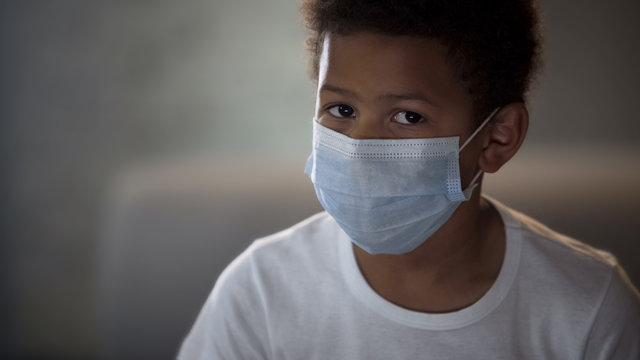 Lonely sick Afro-American boy in face mask on blurred background, quarantine