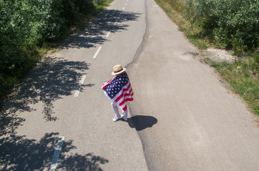 Woman in hat walking with the American flag