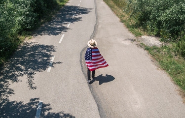 man in hat walking with the American flag on a lonely road.