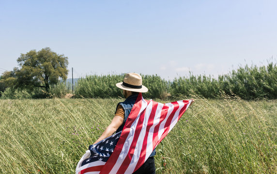 Man with hat and a American flag on a lonely road