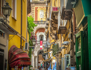 Fototapeten Schmale Gasse Narrow alley with Duomo steeple on the background in Sorrento