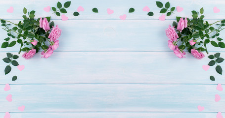 Top view of pink roses with paper hearts on background of shabby wooden planks