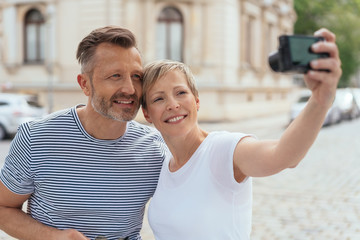 Middle-aged couple posing for a selfie in town