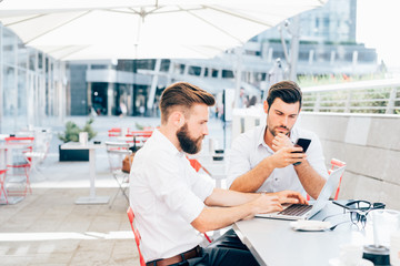 two bearded young business young men outdoor using laptop and smart phone remote working - finance, trading online, wifi technology concept