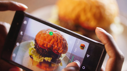 Cell phone photographing a burger. Hamburger on cafe table