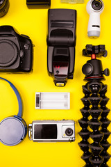 Top view flatlay of summer vacation photographer kit on yellow background