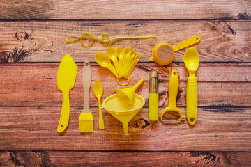Various yellow kitchen utensils on wooden background, top view