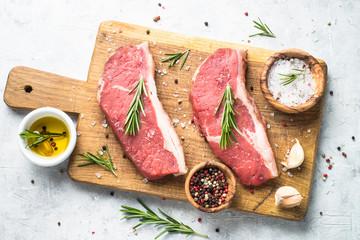 Raw beef striploin steak on cutting board.