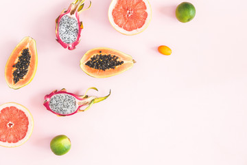 Summer fruits. Tropical pineapple, coconut, papaya, dragon fruit, orange on pastel pink background. Flat lay, top view, copy space