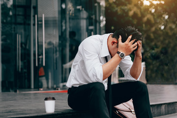 Asian young businessman stress sitting in front office with his hands covering his head against.