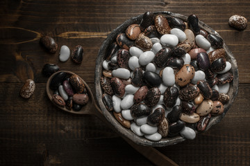 Raw Colorful Beans on Dark Wooden Background