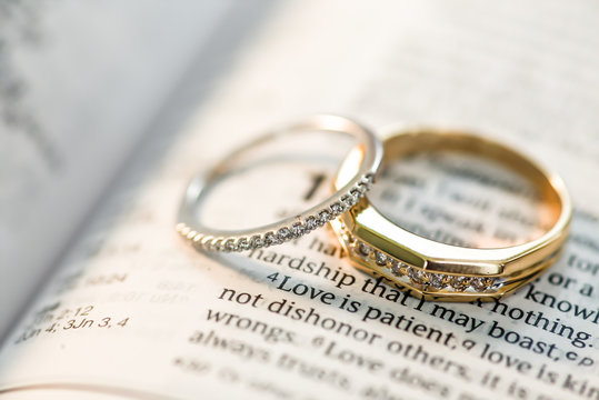 Wedding ring bands sitting on open book Holy Bible Love is patient phrase