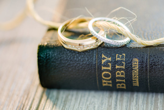 Soft wedding ring bands with diamonds displayed on a black leather Holy Bible