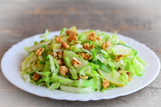Cabbage slaw with pear and walnuts. Quick pear and cabbage slaw on a plate. Vitamin rich food