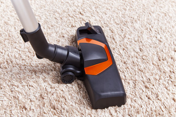 Crop piece of vacuum cleaner in work on top of soft textured carpet surface at home.
