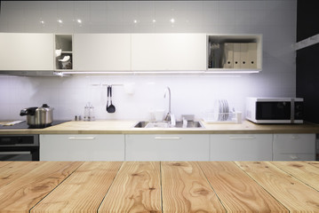 Empty top wooden table and blurred on blur kitchen interior background. For present your products display.