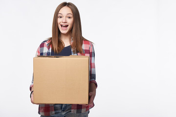 Happy excited woman holding cardboard box with expression of surprise, over white background