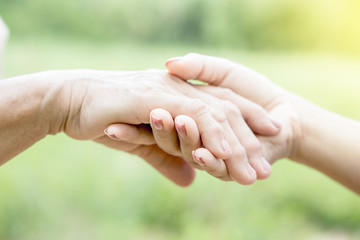close-up of a daughter holding her mother's hand over nature green background