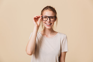 Portrait of cute blond woman 20s wearing basic t-shirt touching eyeglasses and smiling at camera with white perfect teeth, isolated over beige background in studio