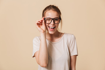 Portrait of beautiful cheerful woman 20s wearing basic t-shirt touching eyeglasses and smiling at camera while winking, isolated over beige background in studio