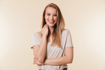 Portrait of charming blonde woman 20s wearing casual t-shirt smiling at camera while touching neck, isolated over beige background in studio