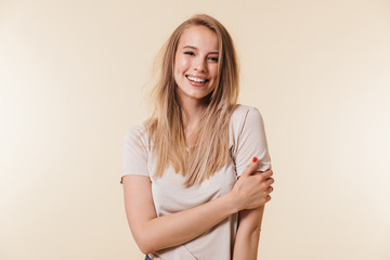 Portrait of beautiful woman 20s with blond hair in basic t-shirt smiling and looking at camera, isolated over beige background in studio