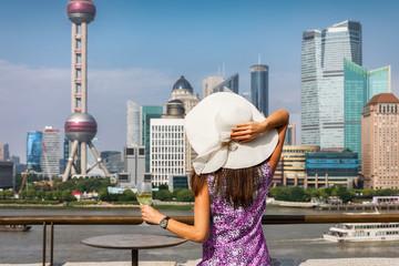 Attraktive Frau mit Sonnenhut genießt ein Glas Wein vor der Skyline von Shanghai, China