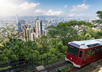 Blick auf die beliebte Peak Tram und die moderne Skyline von Hong Kong an einem sonnigen Tag