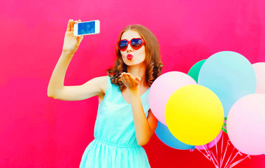 Cool girl taking a picture on a smartphone sends an air kiss over an air colorful balloons a pink background