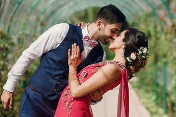 Indian newlyweds hug under green arch in the garden